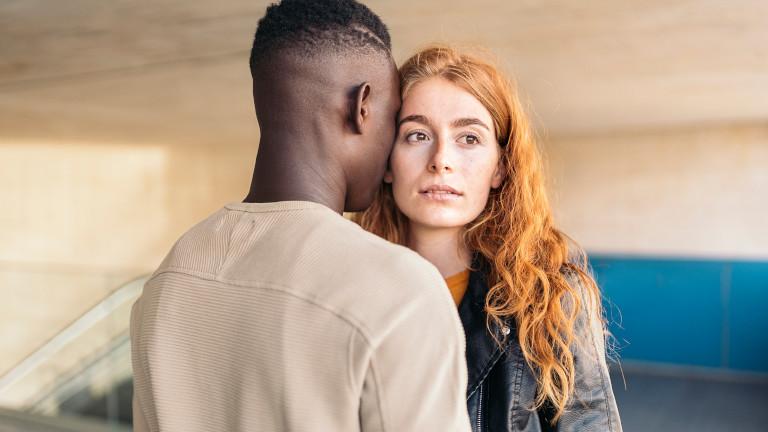 Eine Frau guckt verlassen ins Leere, während ein Mann sich von vorne an sie ranschmiegt