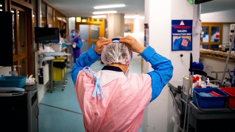Eine Person es medizinischen Fachpersonals setzt sich eine Maske auf, Intensivstation Liege, 13.11.20
