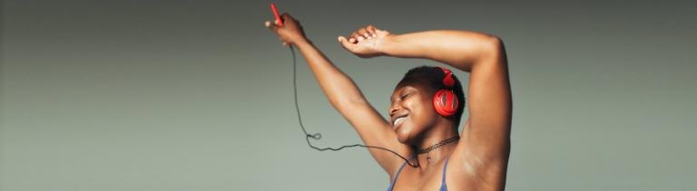 Junge Frau mit Kopfhörern hört Musik und lächelt dabei mit geschlossenen Augen.