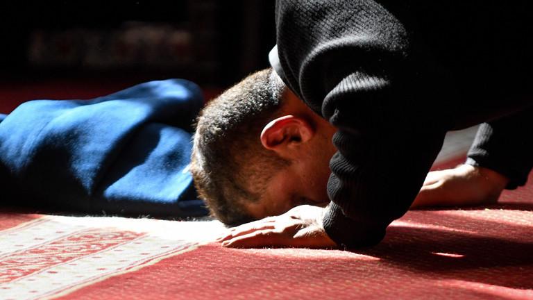 Ein Moslem betet mit dem Kopf am Boden.