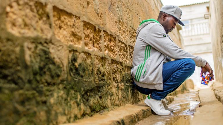 Mann hockt an eine Mauer gelehnt und denkt nach.