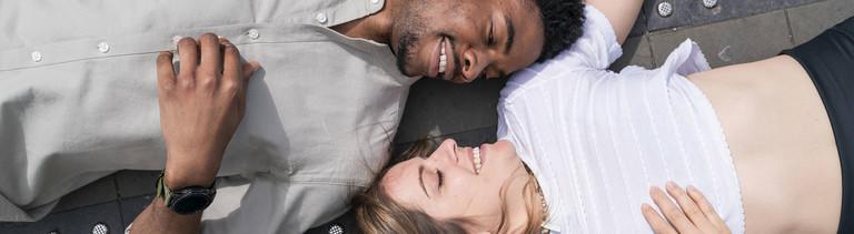 Junges Paar liegt kuschelnd auf dem Boden.