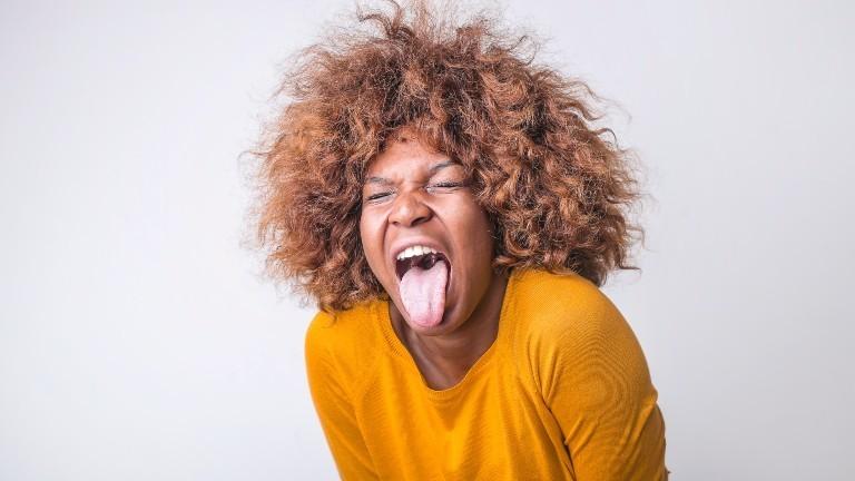 Eine Frau streckt angeekelt die Zunge heraus