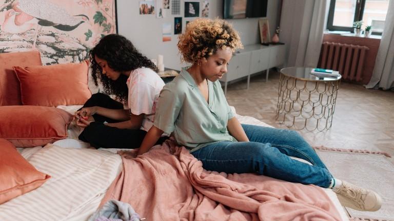 Zwei Schwestern sitzen mit dem Rücken zugewandt auf einem Bett