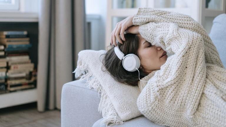 Eine Frau mit Kopfhörern und Wollpulli liegt auf dem Sofa