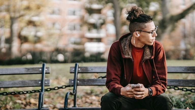 Ein junger Mann sitzt auf einer Bank und schaut nach rechts