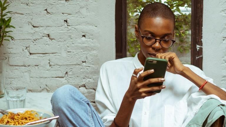 Eine junge Frau sitzt am Essenstisch und schaut in ihr Handy