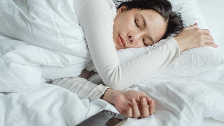 Eine Frau liegt im Bett und schläft, ihr Smartphone liegt daneben