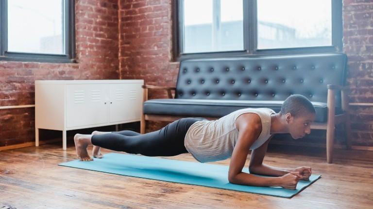 Eine Frau macht eine Plank auf einer Yogamatte