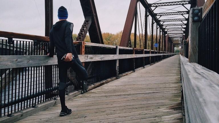 Ein Mann steht an einer Brücke und dehnt sich