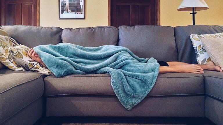 Ein Mann liegt unter einer blauen Wolldecke auf dem Sofa