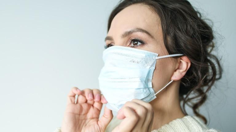 Eine Frau zieht eine Maske auf