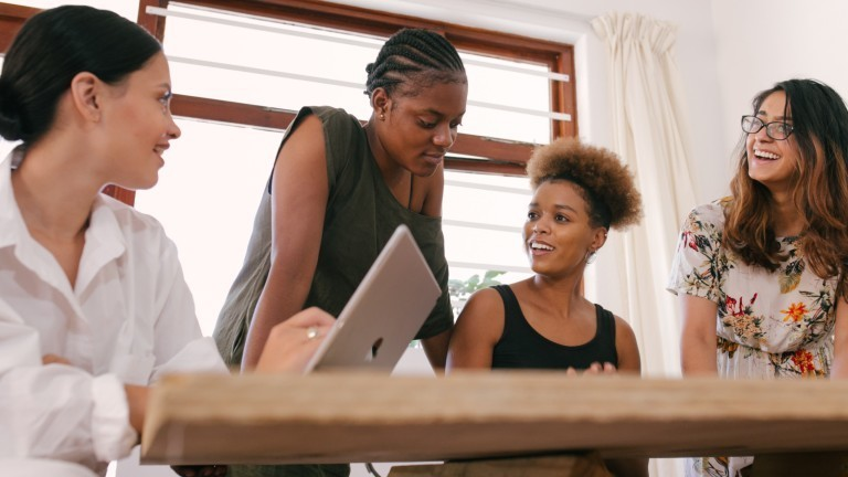 Vier Frauen sitzen an einem Tisch und diskutieren über die Arbeit