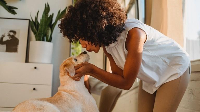 Eine junge Frau macht einen Kussmund zu ihrem Hund