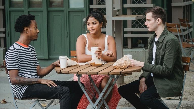 Drei Freund*innen unterhalten sich an einem Tisch bei Kaffee
