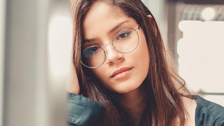 Eine junge Frau schaut mit leeren Augen in die Kamera