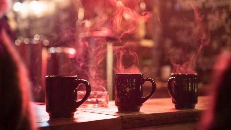 Drei Glühwein Tassen die dampfen