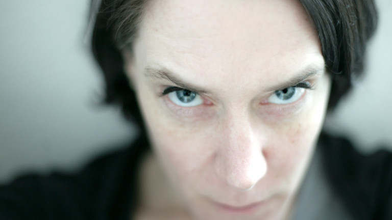 Ein Frau blickt mit Rachegelüsten oder hasserfüllt.