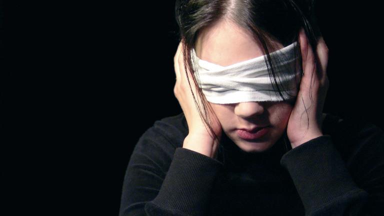 Frau hat die Augen verbunden und hält sich die Ohren zu. Symbolbild für Irrglauben, Nichthören und -sehen