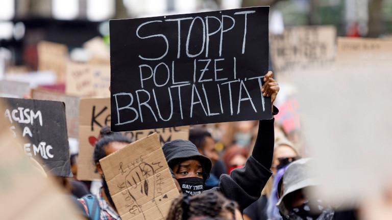 """Demonstrant hält ein Schild hoch, auf dem """"Stoppt Polizei-Brutalität"""" steht"""