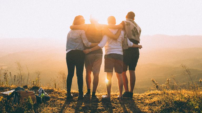 Vier Menschen stehen im Sonnenuntergang und umarmen sich
