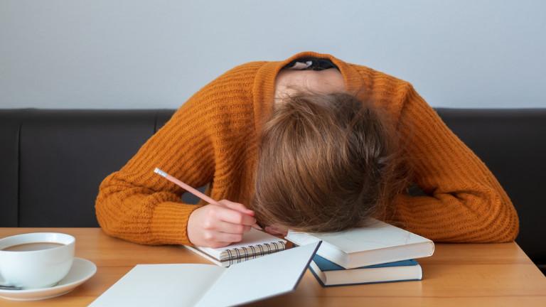 Gestresste Frau legt den Kopf auf den Schreibtisch