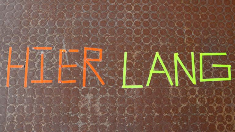 Auf dem Boden ist mit buntem Klebeband ein Satz geklebt: Hier Lang
