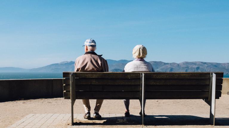 Ein alter Mann und eine alte Frau sitzen auf einer Bank und blicken auf ein Bergpanorama
