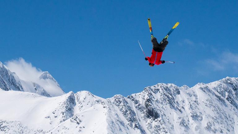Skifahrer fliegt vor Bergpanorama