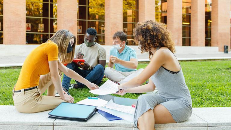Vier Studierende sitzen vor ihren Unterlagen