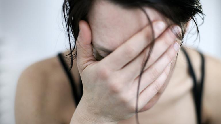 Eine Frau verbirgt ihr Gesicht hinter ihrer Hand.