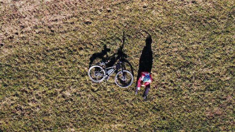 Eine Person sitzt mit dem Fahrrad auf der Wiese.
