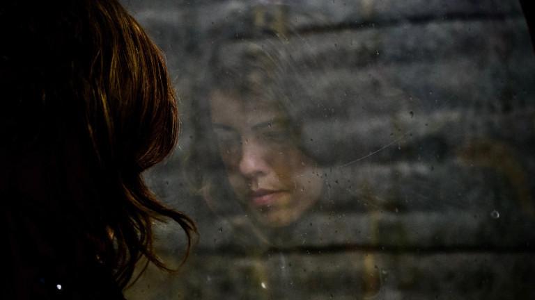 Frau steht traurig am Fenster.