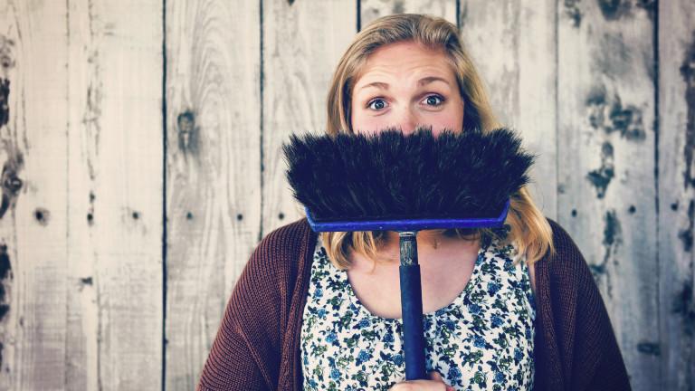 Eine Frau hält sich einen umgedrehten Besen vor den Mund.