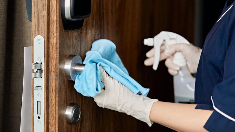 Frau reinigt mit Handschuhen Türgriff