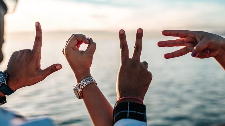 """Männer und Frauen formen mit Fingern """"Love"""""""