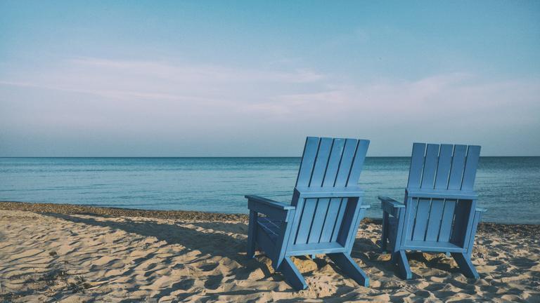 Zwei blaue Sonnenstühle am Meer