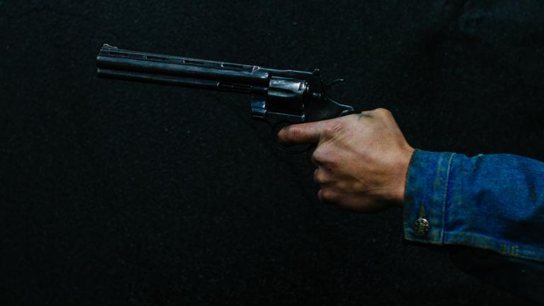 Vor einem dunklen Hintergrund hält jemand eine dunkle Waffe