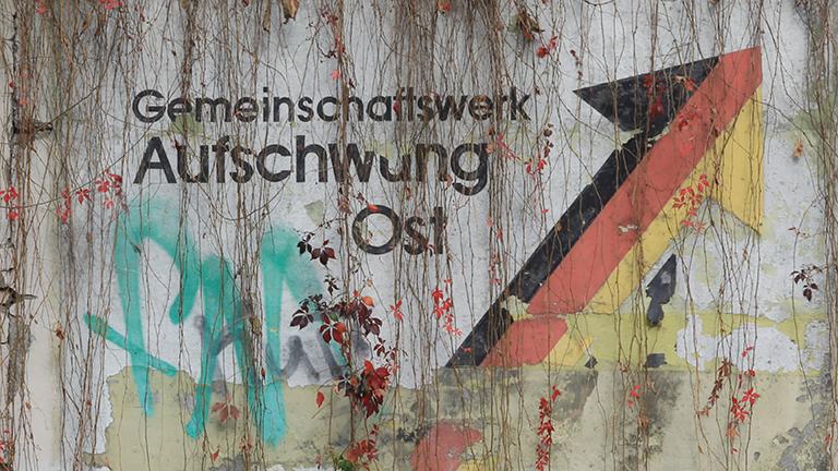 """An einer Schallschutzwand prangt der verwitterte Schriftzug """"Gemeinschaftswerk Aufschwung Ost"""""""