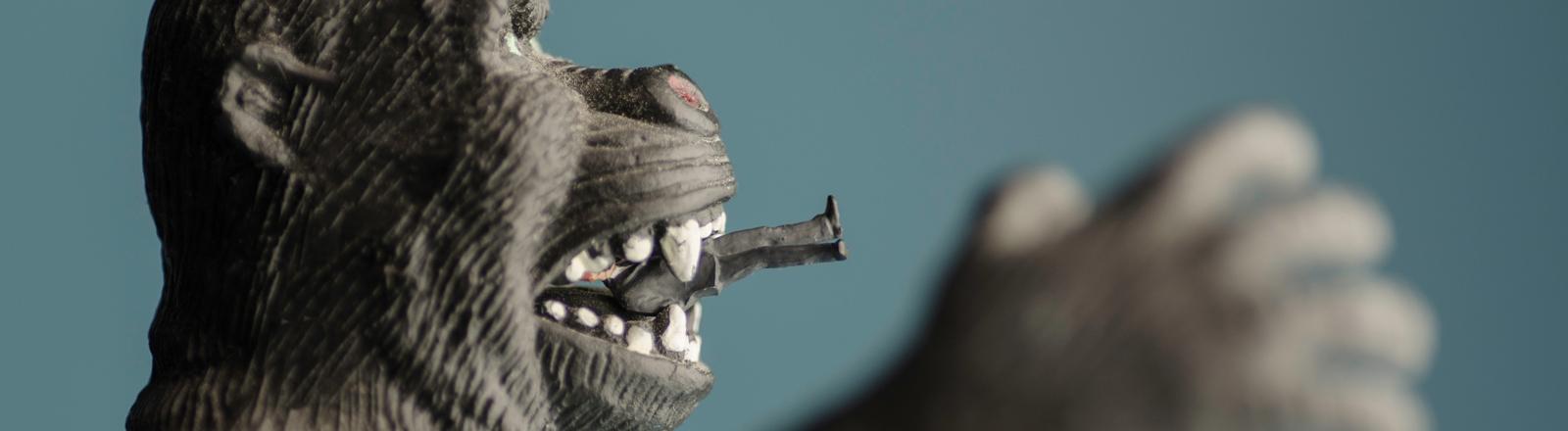 Affenfigur mit Männchen im Maul