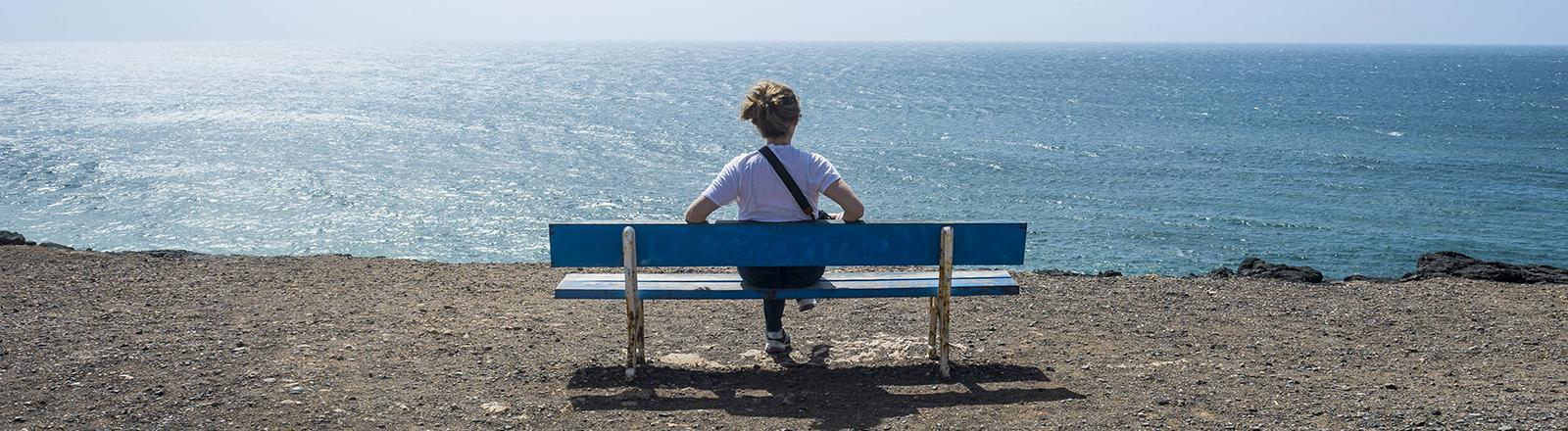 Frau allein auf einer Bank am Meer