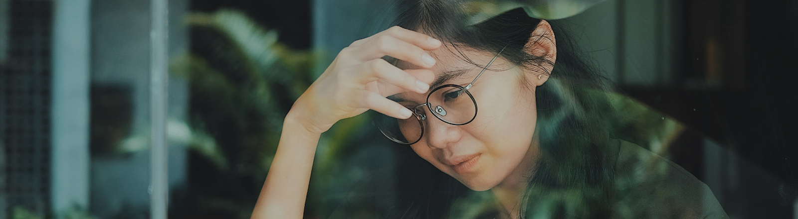 Das Spiegelbild einer grübelnden Frau.
