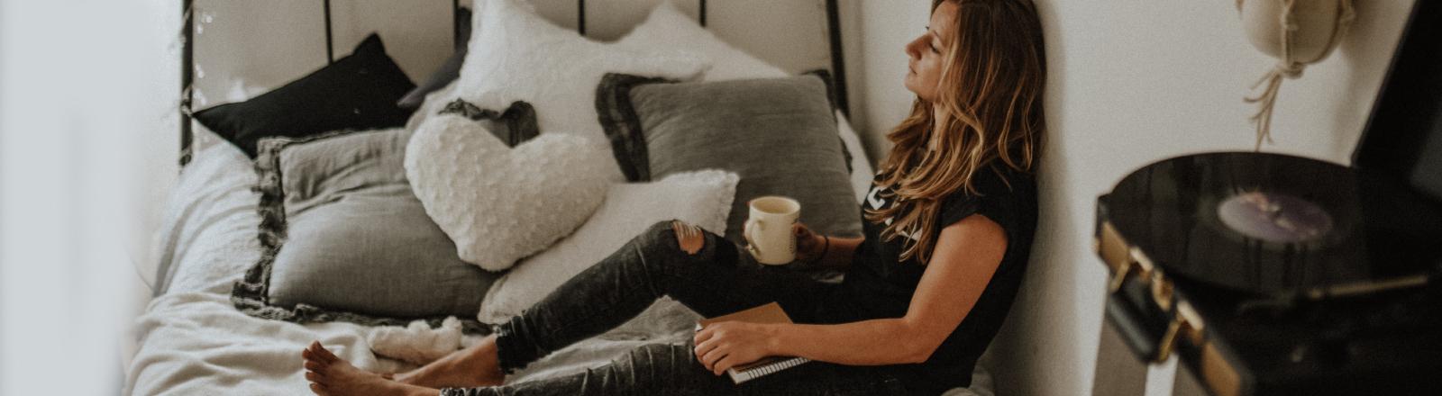 Eine Frau sitzt auf ihrem Bett mit einer Tasse Tee in der Hand