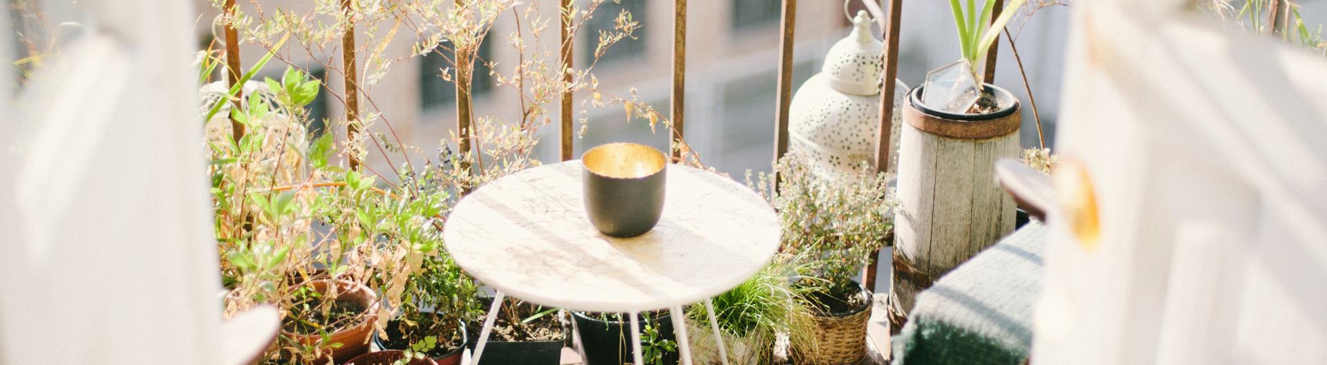 Ein Balkon in der Sonne mit Pflanzen und Deko