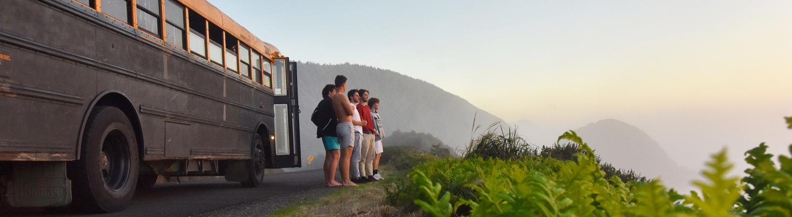 Fünf junge Männer stehen vor einem alten Schulbus und schauen in ein Tal im Sonnenuntergang