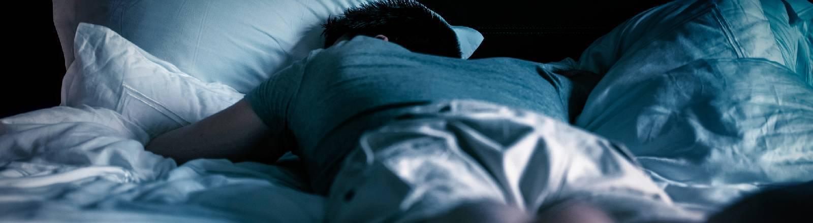 Ein Mann liegt in einem dunklen Zimmer auf einem Bett