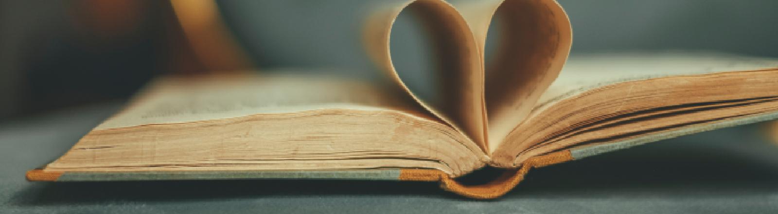 Eine Buchseite formt sich wie ein Herz