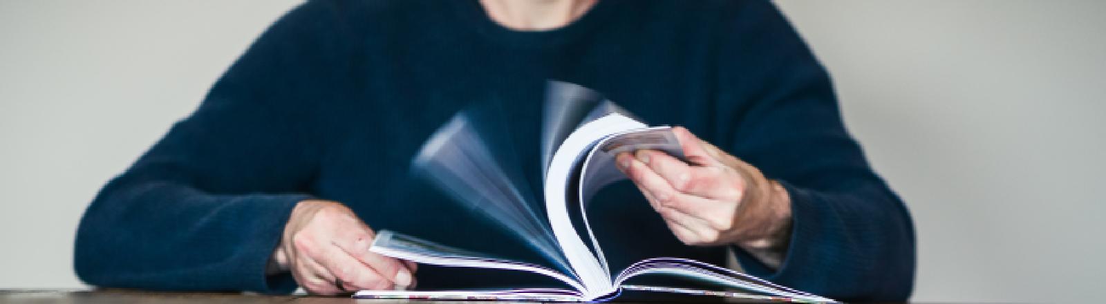 Ein Mann blättert in einem Buch.