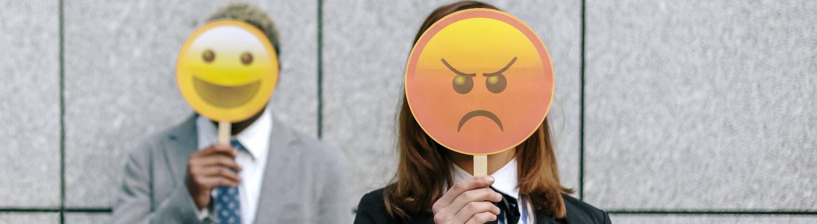 Zwei Menschen mit glücklichen und wütenden Emoji-Masken