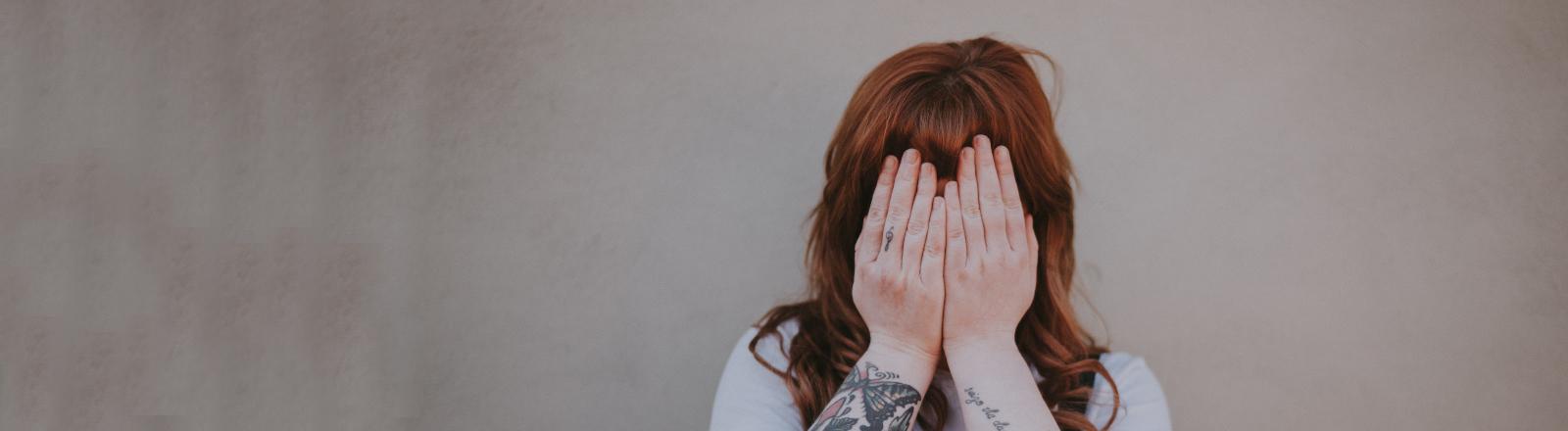 Eine Frau hält sich die Hände vors Gesicht